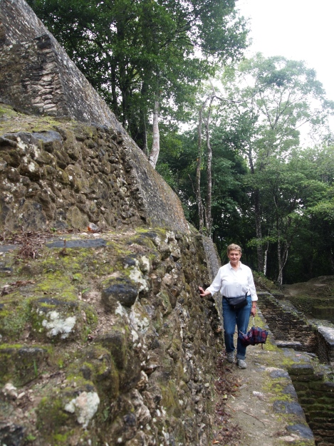 Lucy walking along base of temple on narrow path above courtyard 10 meters below